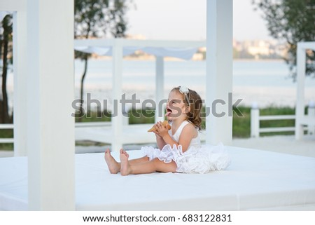 Little girl eating ice cream cone outside. Cute toddler in white dress sitting on the beach #683122831