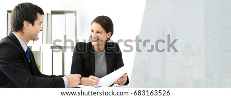Beautiful businesswoman listening and smiling to her colleague at the meeting - panoramic web banner with copy space