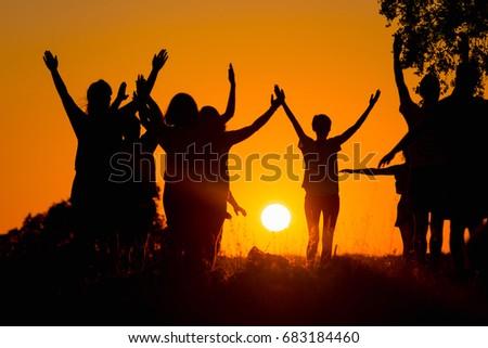 Silhouette of several people practicing yoga in the field #683184460