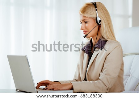 Beautiful smiling woman with a headset on her head using laptop at the office. #683188330