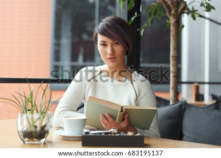 Stylish girl sitting at table in cafe holding book and looking at camera.  #683195137