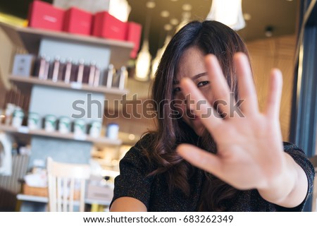 An Asian woman showing her hand sign cover her face to say no to someone with feeling funny in restaurant #683262349
