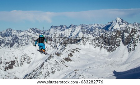 skier jumps with mountains in the back #683282776