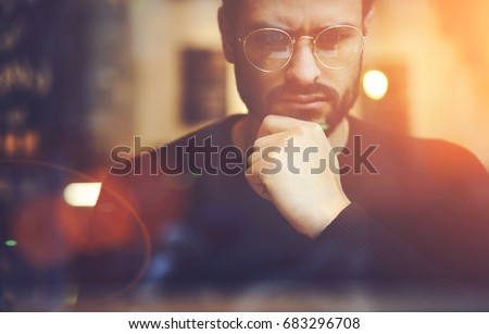 Cropped close up image of pensive bearded entrepreneur in optical spectacles for better views dressed in black sweatshirt.Pondering businessman in trendy eyeglasses thinking on blurred background #683296708
