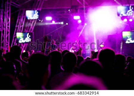 Silhouettes of concert crowd in front of bright stage lights #683342914