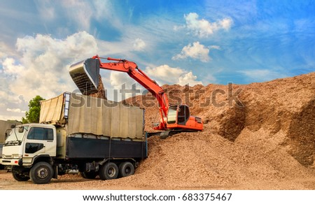 A powerful backhoe loading wood chips onto trucks for exporting. Wood chips for paper production. #683375467