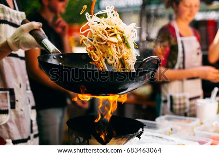 Man cooks noodles on the fire #683463064