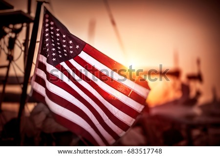 Flag of United States of America flutters in the winds in mild sunset light, independence day of America Royalty-Free Stock Photo #683517748