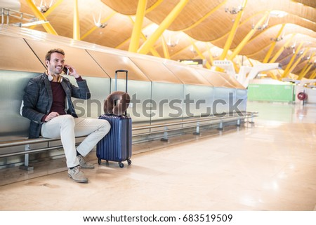 Young man waiting listening music and using mobile phone at the airport with a suitcase #683519509