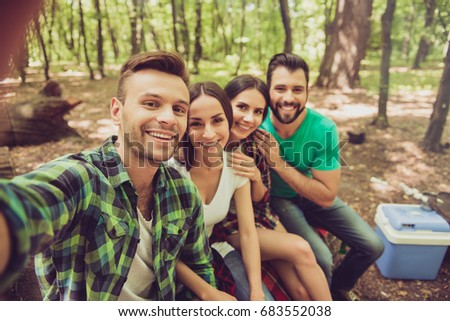 Close up of four happy friends tourists in the spring nice wood, embracing, posing for a selfie shot, that handsome blond guy is taking, sitting on a log #683552038