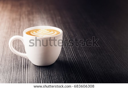 Close up white coffee cup with heart shape latte art foam on black wood table near window with light shade on tabletop at cafe. #683606308