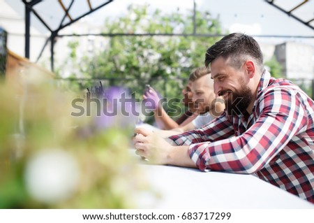 Side view of a cute young man with a beard in a red checkered shirt smiling and typing text in a smart phone next to his fellow friends who also work with a smart phone and sit on an open terrace #683717299
