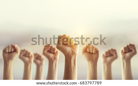 Peoples raised fist air fighting and sunlight effect, Competition, teamwork concept, background space for text. #683797789