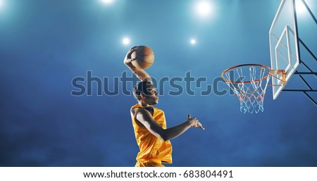 Close up image of professional basketball player making slam dunk during basketball game in floodlight basketball court. The player is wearing unbranded sport clothes. #683804491