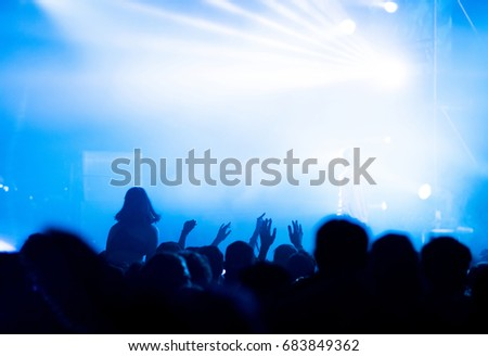 Rear view of crowd with arms outstretched at concert. Bright stage lights in the background #683849362