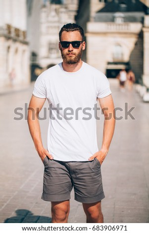 Hipster handsome male model with beard  wearing white blank  t-shirt with space for your logo or design in casual urban style #683906971