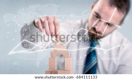 Young handsome businessman using wooden building blocks with data and calculations behind him #684111133