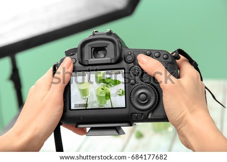Young woman photographing juice in photo studio, closeup #684177682