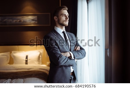Young handsome man relaxing at his apartment in a hotel after business meeting. Business trip. Booking hotel during your vacation. Businessman in luxury room  of the expensive beautiful hotel.  #684190576