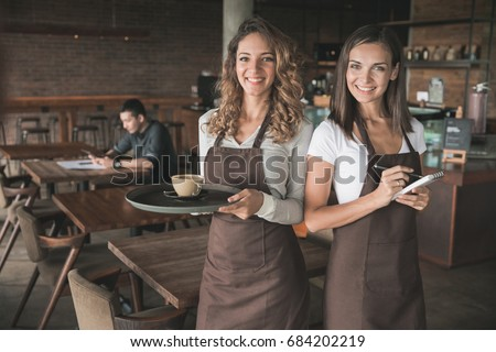 portrait of two beautiful female waitress smiling to camera #684202219