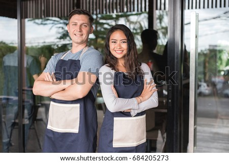 Successful male and female small business owner proudly standing in front of their cafe or coffee shop #684205273