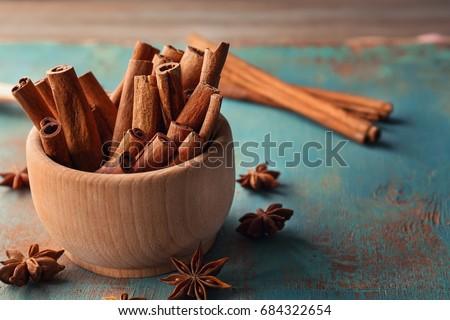 Wooden bowl with cinnamon sticks and anise on table Royalty-Free Stock Photo #684322654