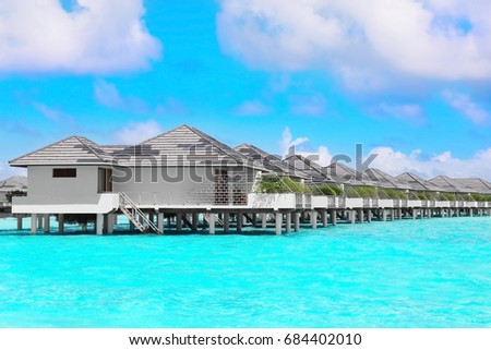 Modern beach houses on piles at tropical resort #684402010