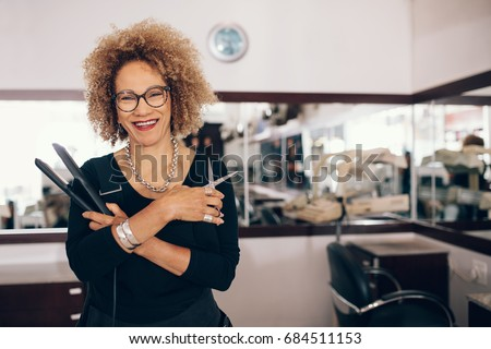 Professional hair stylist holding a hair straightener and scissors. Woman hairdresser in happy mood at the salon. Royalty-Free Stock Photo #684511153