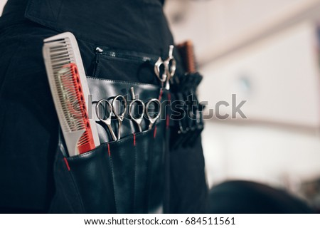 Closeup of scissors and combs in a salon holster pouch. Hairdressing tools inside a hairdresser waist pouch. Royalty-Free Stock Photo #684511561