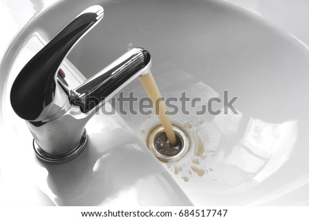 Water tap faucet with flowing contaminated muddy and dirty water in a white bathroom sink. #684517747