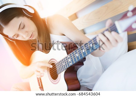 beautiful smart caucasuan girl playing music on the bed with happiness and guitar #684543604