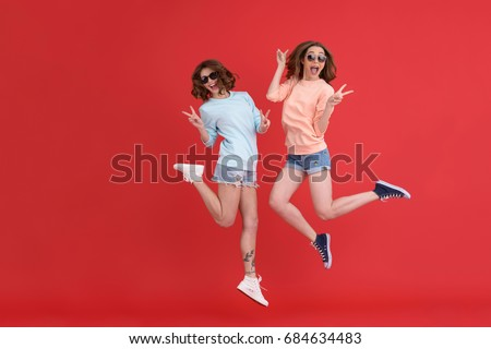 Image of young cheerful ladies friends jumping isolated over red background. Looking at camera. #684634483