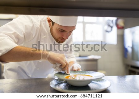food cooking, profession and people concept - happy male chef cook serving plate of soup at restaurant kitchen #684711121