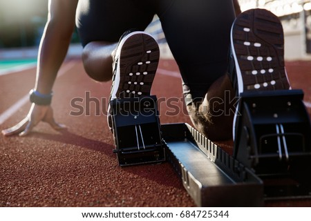 Back view of men's feet on starting block ready for a sprint start Royalty-Free Stock Photo #684725344