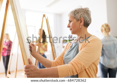 art school, creativity and people concept - happy senior woman artist with easel and pencil drawing picture at studio Royalty-Free Stock Photo #684728362