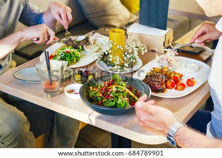 At the table, two men eat dinner, eat a steak, with a salad on a white plate, with a fork and knife in their hands. Close up. #684789901