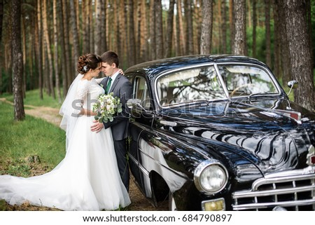 luxury elegant wedding couple holding hands on background of stylish black car . gorgeous bride and handsome groom in retro style. romantic moment #684790897