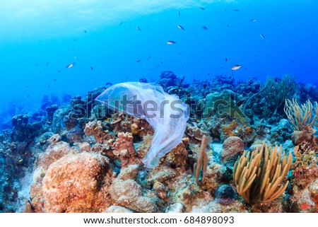 Plastic pollution:- a discarded plastic rubbish bags floats on a tropical coral reef presenting a hazard to marine life Royalty-Free Stock Photo #684898093