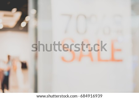 Shopping center with customers and seasonal sale promotions. Blurred, people unrecognizable #684916939