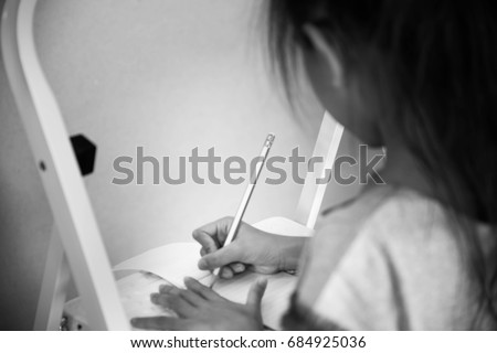 Blurry little girl writing alone,Selective focus,Black and white