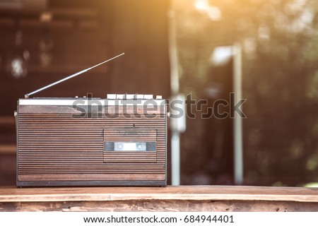 Retro radio cassette stereo on wooden table in vintage color tone #684944401