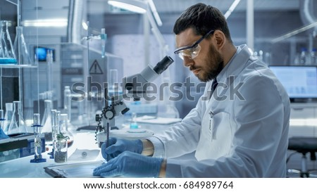 In a Modern Laboaratory Research Scientist Writes Down His Experiment Observations. #684989764