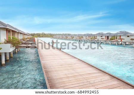 View of wooden pontoon and beach houses at sea resort #684992455