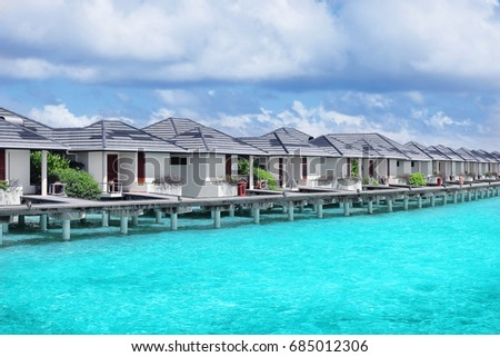 Modern beach houses on piles at tropical resort #685012306
