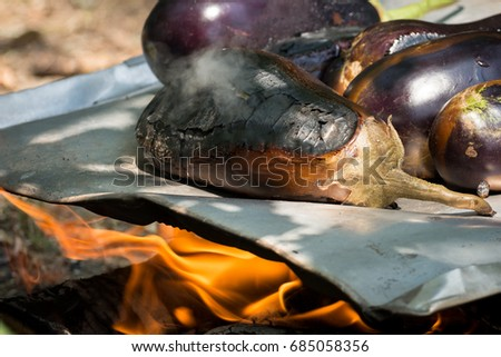 Eggplants roasting on a metal sheet above the fire outdoor. #685058356