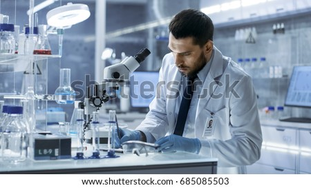 Research Scientist Writes Down Observations. He's Conducts Experiments in Modern Laboratory. #685085503