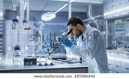 Research Scientist Looks into Microscope. He's Conducts Experiments in Modern Laboratory. #685086646