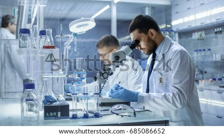 In a Modern Laboratory Two Scientists Conduct Experiments. Chief Research Scientist Adjusts Specimen in a Petri Dish and Looks on it Into Microscope. Royalty-Free Stock Photo #685086652