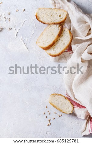 Homemade white wheat bread slice served with flour and wheat grain seeds on white linen towel over gray texture background. Top view with space. #685125781