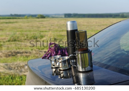 Items for alternative brewing of coffee in travel on the trunk of a black car. On the background of the summer landscape in the field #685130200